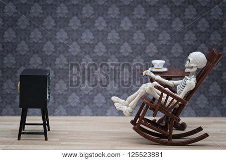 a skeleton sitting on a rocking chair watching tv