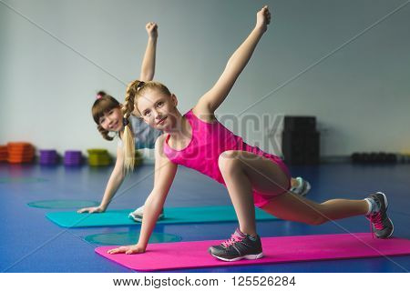 Girls doing gymnastic exercises or exercising in fitness class.