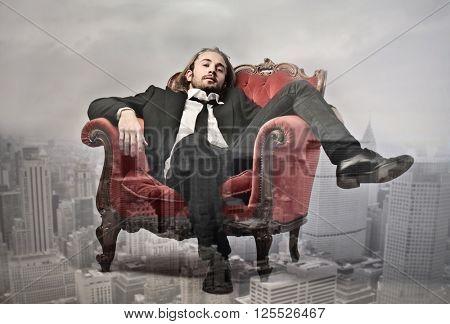 Rich businessman sitting in red chair