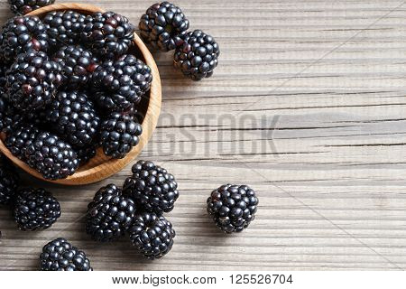 Fresh blackberries in bowl on wooden background. Close up top view high resolution product. Harvest Concept