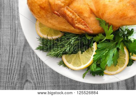 Roast chicken with parsley and lemon on grey wooden background.