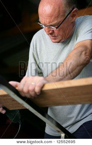 Portrait of a senior man sanding a board