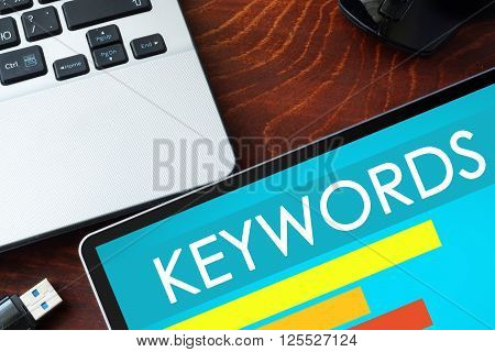 Tablet with word Keywords  on a wooden background.
