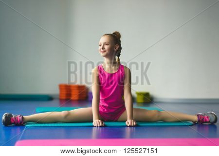 Girl sat and makes stretching or gymnastic exercises in the class for fitness.