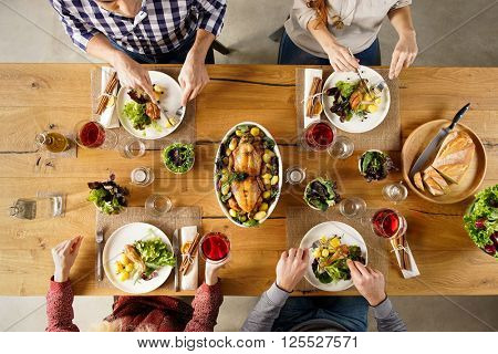 Top view of dining table with salad and roasted chicken with potatoes. High angle view of happy young friends having lunch at home. Men and women eating lunch together.