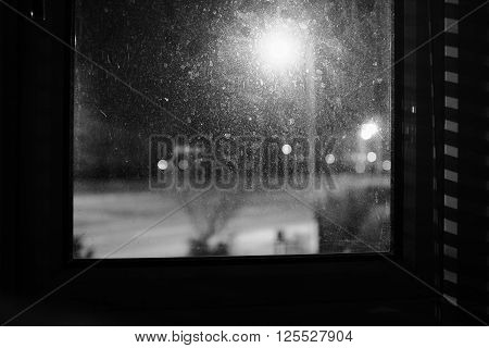 High-contrast, black-and-white image of a grimy window (with a defocused view of the road and street lights outside) just off-centre.