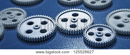 Several Gear wheels in a row on blue background