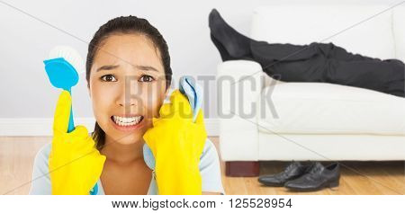 Distressed woman holding cloth and scrubbing brush against low section of businessman resting on sofa in living room