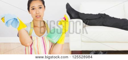 Weary woman with spray bottle and rag against low section of businessman resting on sofa in living room
