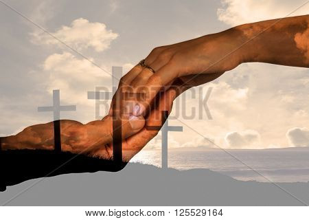Cropped hand of couple holding hands against cross religion symbol shape over sunset sky