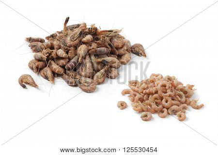 Heap of peeled and unpeeled brown shrimps on white background
