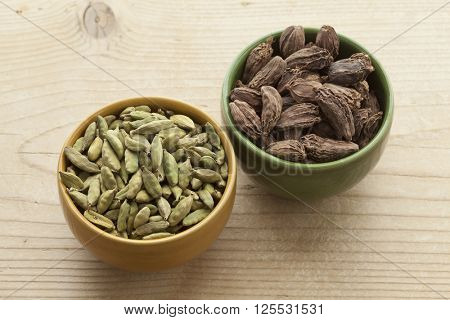 Bowls with green and large black Cardamom seeds