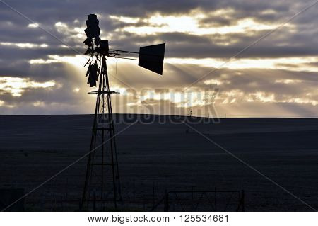 Landscape with water pump windmill at sunrise