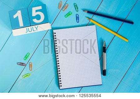 July 15th. Image of july 15 wooden color calendar on blue background. Summer day. Empty space for text.