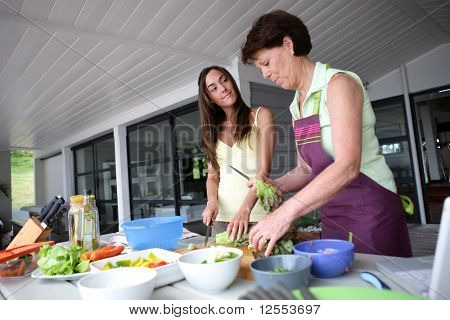 Portrait of a senior woman and a young woman cooking