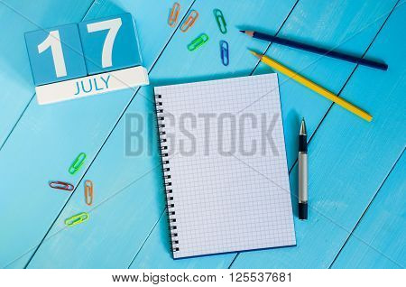 July 17th. Image of July 17 wooden color calendar on blue background. Summer day. Empty space for text.