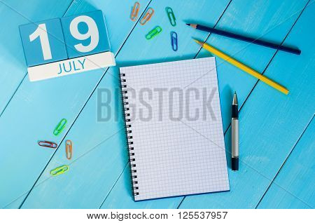 July 19th. Image of July 19 wooden color calendar on blue background. Summer day. Empty space for text.