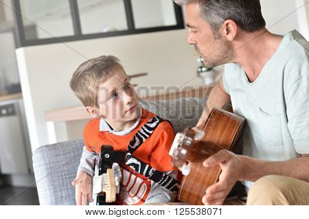 Daddy with son playing the guitar