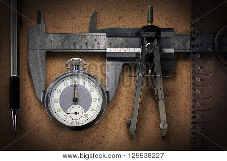 Pocket watch with engineering tools pencil calipers ruler on wooden desk