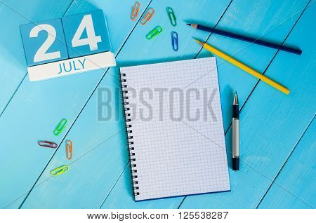 July 24th. Image of july 24 wooden color calendar on blue background. Summer day. Empty space for text.