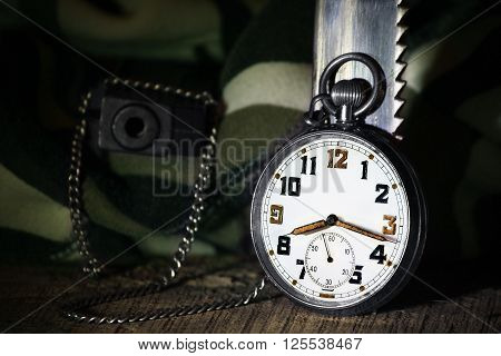 Pocket watch with gun and knife camuflage on wooden