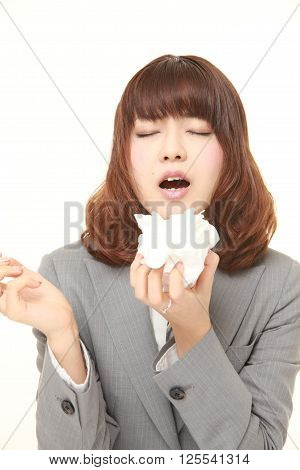 young businesswoman with an allergy sneezing into tissue