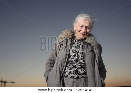 Portrait Of A Senior Woman Over Sunset Sky