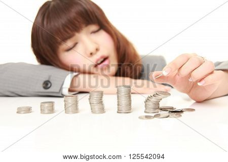 stack of coins collapsed when businesswoman put a coin