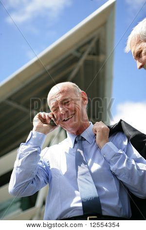 Portrait of a senior man in suit smiling on phone