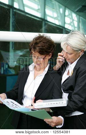 Portrait of a senior woman phoning next to a senior woman holding documents
