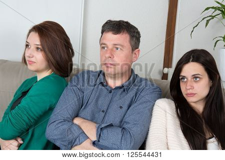 Father Reprimending His Daughters Seated On A Sofa