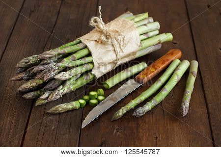 Fresh asparagus spears with knife on a wooden table