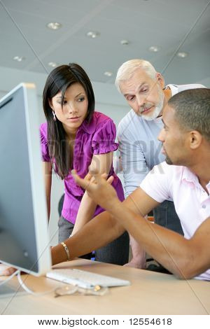 Portrait of a young woman and men in front of a desktop computer