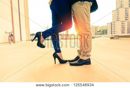 Lovers couple on date kissing and hugging on urban background at sunrise - Man and woman legs closeup outdoor - Concept of a romantic love story with vintage nostalgic filter look and warm tone