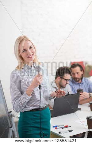 Happy business woman using microphone for presentation on new business strategy in office to her collegues men.