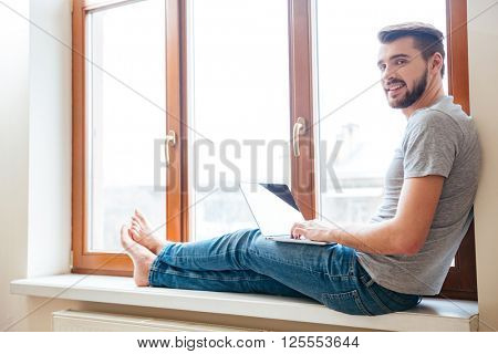 Smiling relaxed young man using laptop sitting on window sill