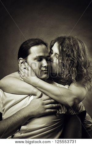 Young pretty girl kissing her boyfriend over dark background