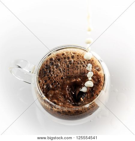 Pouring process of milk into glass cup full of cocoa splashes drops and froth around glass cup against white background
