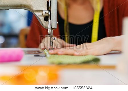 Close up of hands of unrecognizable tailor woman working with old sewing machine