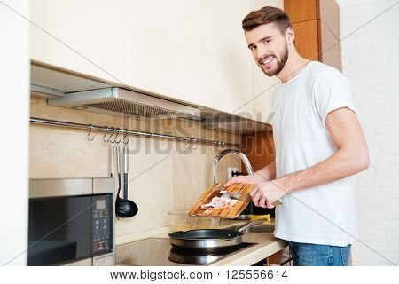 Cheerful handsome young man frying meet using pan and smiling