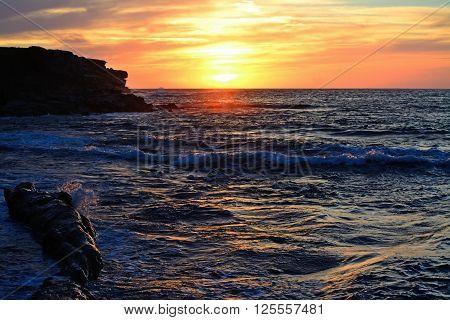 rocks in the water in Porto Ferro at sunset Sardinia