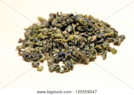 Piles of dried green tea leaves isolated on white background
