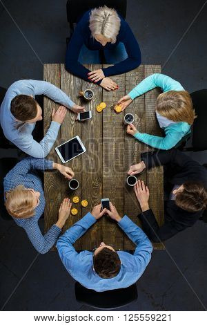 Top view creative photo of business people sitting at dark wooden vintage table. Business people having meeting. Concept for successful teamwork. There are electronic gadgets at table