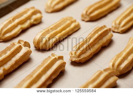 Homemade eclairs or profiterole dessert food on baking sheet background