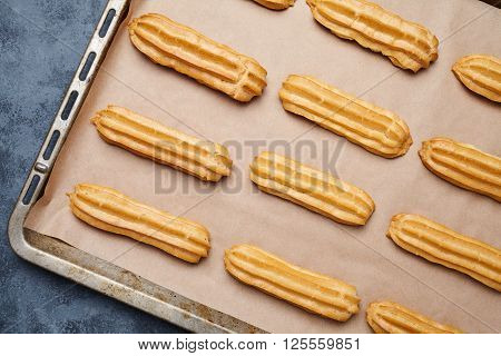 Eclairs or profiterole traditional French cuisine filled with whipped cream on baking sheet background
