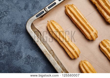 Eclairs traditional French pastry on baking sheet with empty frame template for design text