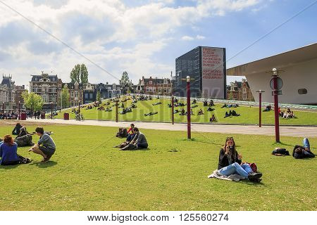 Amsterdam, Netherlands - May 6: This is the Museum square with a building the Stedelijk Museum and the lawn with vacationers people May 9, 2013 in Amsterdam, Netherlands.