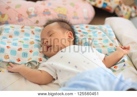Cute Asian Newborn Baby Sleeping On Bed