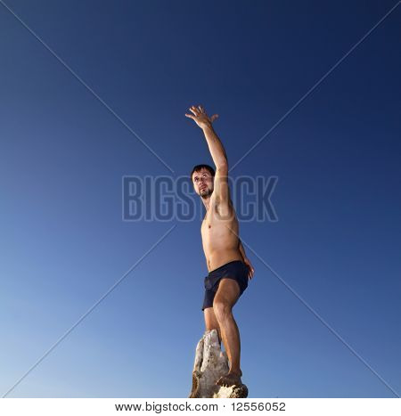 Photo of young acrobat man with blue sky at background