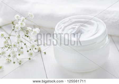 Anti wrinkle anti-aging cosmetic cream skincare and face care moisture lotion with herbal flowers in glass jar with towel on white background